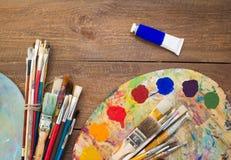 Farben, Bürsten und Palette auf dem hölzernen Hintergrund Stockfoto