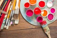 Farben, Bürsten und Palette auf dem hölzernen Hintergrund lizenzfreie stockfotografie