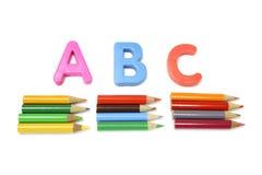 Farben-Bleistifte und Alphabete Stockfotos