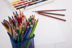 Farben, Bleistifte und Bürsten auf hölzernem zu einem Boden Bildaufbereitung Lizenzfreies Stockfoto