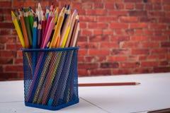 Farben, Bleistifte und Bürsten auf hölzernem zu einem Boden Bildaufbereitung Lizenzfreie Stockfotos