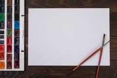Farben, Bleistifte und Bürsten auf hölzernem zu einem Boden Bildaufbereitung Stockfotografie