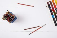 Farben, Bleistifte und Bürsten auf hölzernem zu einem Boden Bildaufbereitung Stockbild