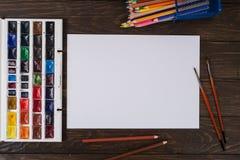 Farben, Bleistifte und Bürsten auf hölzernem zu einem Boden Bildaufbereitung Stockbilder