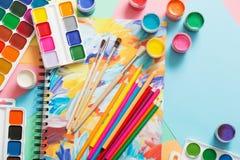 Farben, Bleistifte und Bürsten auf Papier Lizenzfreies Stockfoto
