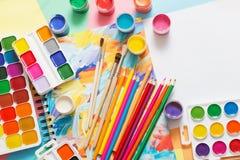 Farben, Bleistifte und Bürsten auf Papier Stockfotografie