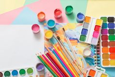 Farben, Bleistifte und Bürsten auf Papier Lizenzfreie Stockfotografie