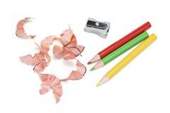 Farben-Bleistifte und Schnitzel Stockfotos