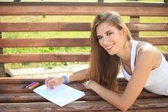 Farben des jungen Mädchens in einem Park, der auf einer Bank sitzt Lizenzfreie Stockbilder