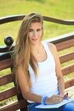 Farben des jungen Mädchens in einem Park, der auf einer Bank sitzt Stockfoto