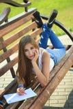 Farben des jungen Mädchens in einem Park, der auf einer Bank sitzt Lizenzfreie Stockfotos