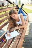 Farben des jungen Mädchens in einem Park, der auf einer Bank sitzt Stockbilder