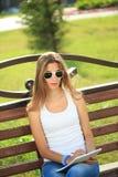 Farben des jungen Mädchens in einem Park, der auf einer Bank sitzt Stockfotos