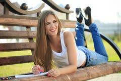 Farben des jungen Mädchens in einem Park, der auf einer Bank sitzt Stockfotografie