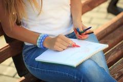 Farben des jungen Mädchens in einem Park, der auf einer Bank sitzt Lizenzfreies Stockbild