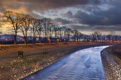Farben des Riverbank während des drastischen Sonnenuntergangs Stockfotografie