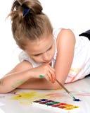Farben eines kleinen Mädchens mit Farbe und Bürste Lizenzfreie Stockfotos