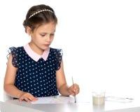 Farben eines kleinen Mädchens mit Farbe und Bürste Stockfoto