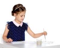 Farben eines kleinen Mädchens mit Farbe und Bürste Lizenzfreie Stockbilder