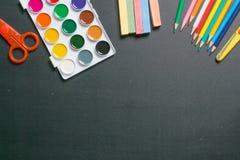 Farben, Scheren, Bleistifte und Kreiden auf schwarzer Tafel 1 Stockbilder