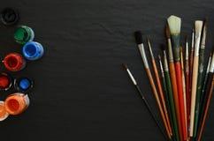 Farben und Bürsten auf einer Tabelle Stockbild