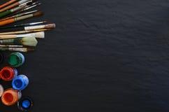 Farben und Bürsten auf einer Tabelle Lizenzfreie Stockfotografie