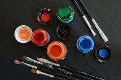Farben und Bürsten auf einer Tabelle Stockfotografie