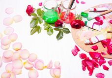 Farben und Bürsten mit den rosafarbenen Blumenblättern Arbeitsplatz des Künstlers, Designer Stockfoto