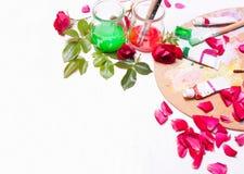 Farben und Bürsten mit den rosafarbenen Blumenblättern Arbeitsplatz des Künstlers, Designer Stockfotos