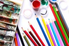 Farben und Bleistifte auf weißem Hintergrund Lizenzfreie Stockfotos