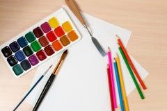 Farben und Bleistifte für das Zeichnen sind um einen Schiefer der freien Räume Lizenzfreies Stockfoto