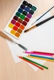 Farben und Bleistifte für das Zeichnen sind um einen Schiefer der freien Räume Lizenzfreie Stockbilder