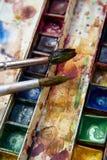 Farben und kindisches Malzeug, Aquarelle und Bürsten, Wasserfarbfarben Stockfotos