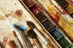 Farben und kindisches Malzeug, Aquarelle und Bürsten, Wasserfarbfarben Stockbild