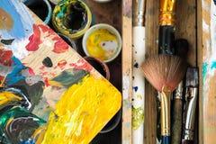 Farben von verschiedenen Farben und von schmutzigen Bürsten auf dem Gestell der Künstlernahaufnahme lizenzfreies stockbild