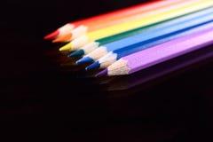 Farbenbleistifte auf dunklem Glas Stockbilder