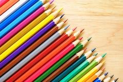 Farbenbleistifte auf hölzernem Hintergrund Lizenzfreie Stockfotos