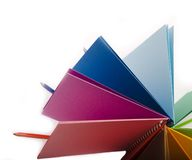 Farbenbleistifte und farbiges Notizbuch Stockfotos