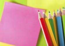Farbenbleistifte und -post-It für Anzeigenanmerkung Stockfotografie