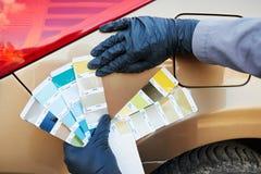 Farbenkünstlermann, der Farbe des Autos mit zusammenpassenden Proben der Farbe vorwählt Lizenzfreies Stockfoto