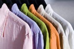 Farbenleinenhemden auf Aufhängungen Lizenzfreies Stockfoto