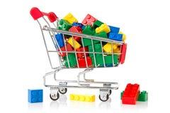 Farbenplastikziegelsteine in einem Einkaufswagen Stockfotos