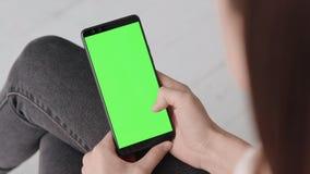 Farbenreinheitsschlüsselmodell mit grünem Schirm am Handy der jungen Frau zu Hause stock footage