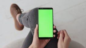 Farbenreinheitsschlüsselmodell mit grünem Schirm am Handy der jungen Frau zu Hause stock video footage