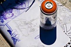 Farbenspraydose und eine Skizze Stockbilder
