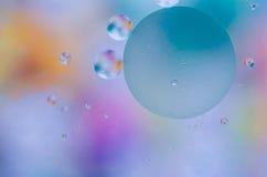 Farbige Öltröpfchen auf der Wasseroberfläche Lizenzfreie Stockbilder