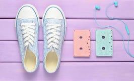 Farbige Audiokassetten, Kopfhörer, Turnschuhschuhe auf einem purpurroten Pastellhintergrund Altmodische Technologien Lizenzfreie Stockbilder