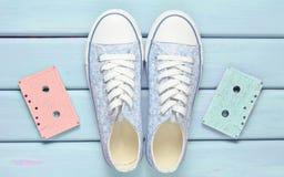 Farbige Audiokassetten, Turnschuhschuhe auf einem purpurroten Pastellhintergrund Altmodische Technologien Beschneidungspfad einge Lizenzfreies Stockfoto