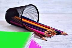 Farbige Auflagen und farbige Bleistifte in einem Behälter Stockfotografie