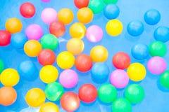 Farbige Bälle, die in Kiddiepool schwimmen Stockbilder